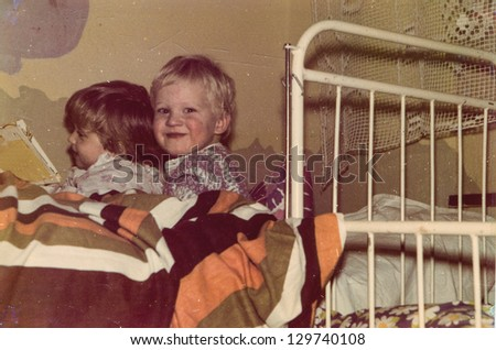 Vintage photo of siblings reading in bed (1985) - stock photo