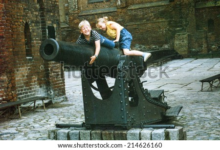 Vintage photo of sister and brother on ancient cannon, eighties - stock photo