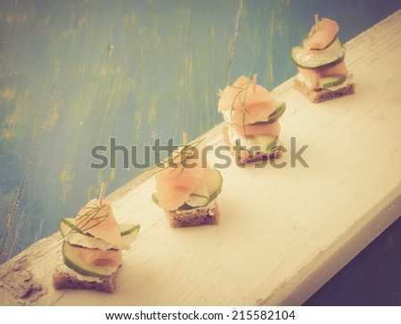 vintage photo of small sandwiches with salmon and cream cheese - stock photo