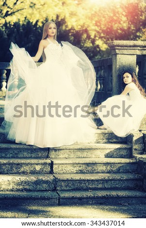 Vintage photo of standing blonde bride in white tulle lush dress and cute brunette curly little girl in nice gown sitting on stone stairs in autumn park, vertical picture - stock photo