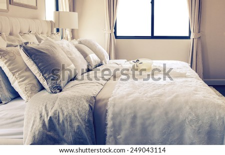 Vintage photo of stylish bedroom interior design with white and grey pillow on bed - stock photo