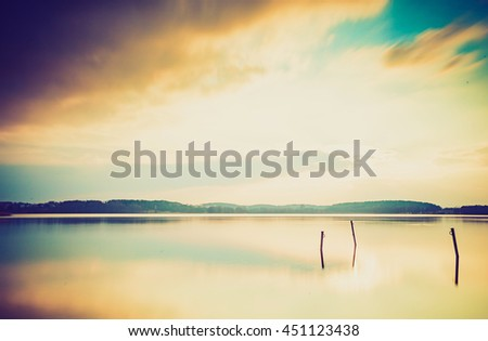 Vintage photo of sunset over calm lake in Poland. Old photo of lake sunset. - stock photo