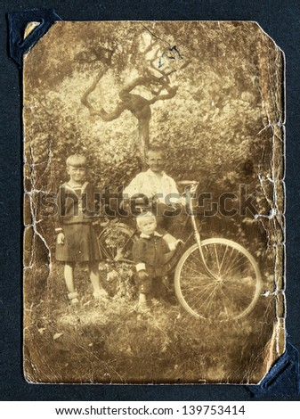 Vintage photo of three children with a bike (thirties) - stock photo