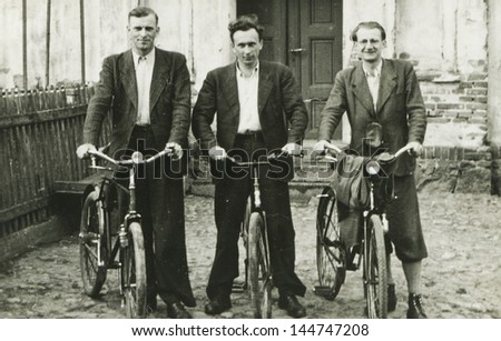 Vintage photo of three men with bicycles, forties - stock photo