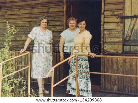 Vintage photo of three women on terrace (seventies) - stock photo