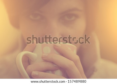 Vintage photo of tired woman drinking morning coffee or tea - stock photo