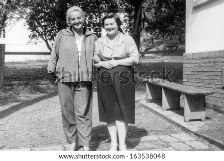 Vintage photo of two adult overweight sisters, fifties - stock photo
