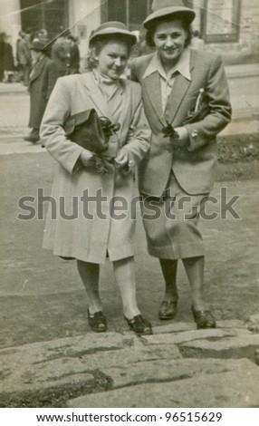 Vintage photo of two elegant women in hats walking (1949) - stock photo