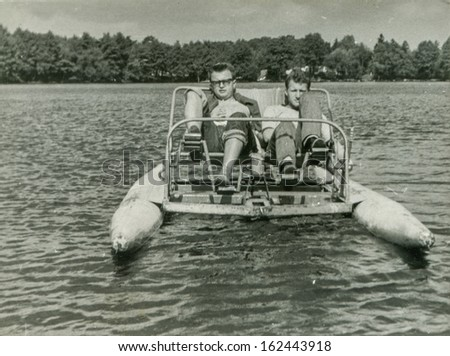 Vintage photo of two men on paddle boat, sixties - stock photo