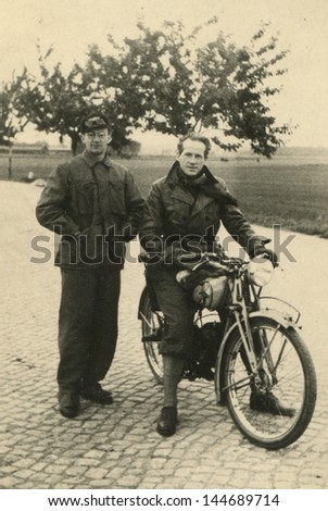 Vintage photo of two men with a motorbike, forties - stock photo