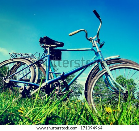 Vintage photo of two old bicycle on the grass - stock photo