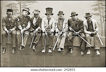 Vintage Photo of Vagabonds Sitting On Fence Wearing Hats - stock photo