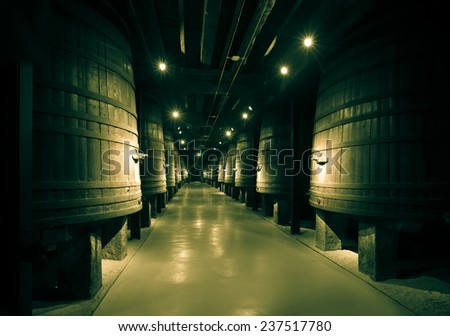 Vintage photo of vertical large  barrels in old cellar - stock photo