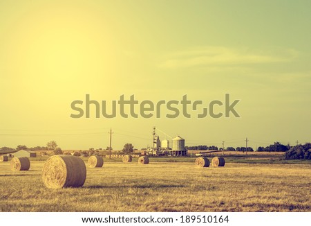 Vintage photo of wheat bales in sunset