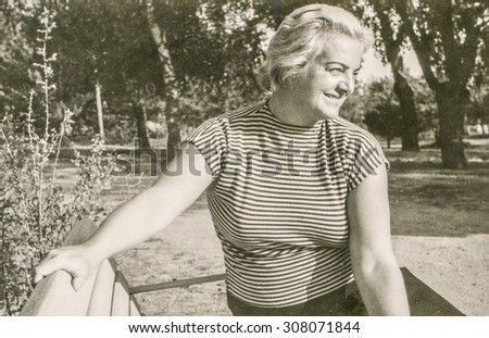 Vintage photo of woman on bench, 1950's - stock photo