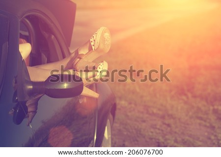 Vintage photo of woman's legs in high heel shoes out of car windows in summer sunset - stock photo