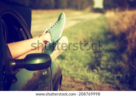 Vintage photo of woman's legs out of car windows - stock photo
