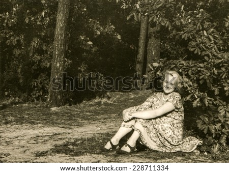 Vintage photo of woman sitting on grass, fifties - stock photo