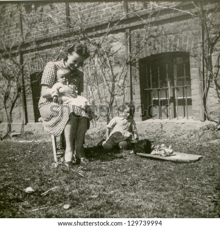 Vintage photo of woman, two little children, hen and chicks (forties) - stock photo