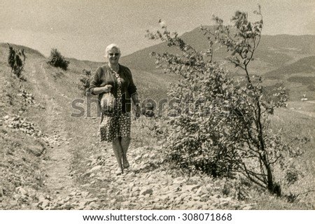 Vintage photo of woman walking in mountains, 1950's - stock photo