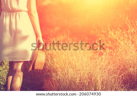 Vintage photo of woman walking in summer sunset  - stock photo