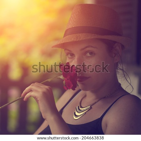 Vintage photo of woman with a red rose - stock photo