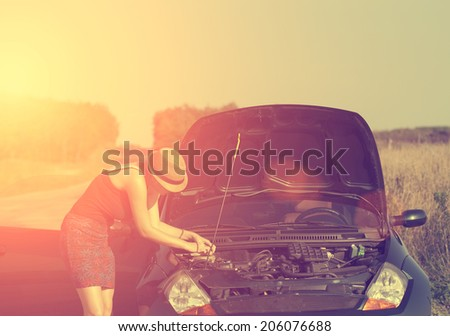 Vintage photo of woman with broken down car in summer sunset - stock photo