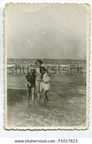Vintage photo of woman with children on beach (fifties)