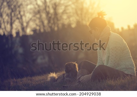 Vintage photo of woman with dog in sunset - stock photo