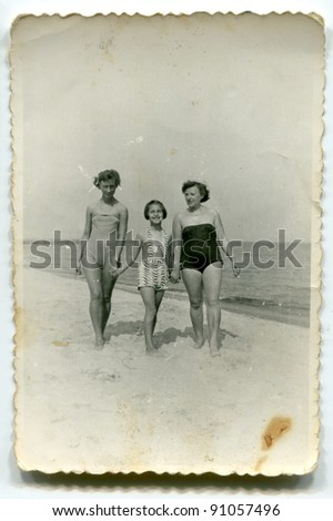 Vintage photo of women and girl on beach (fifties) - stock photo