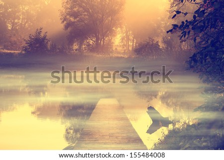 Vintage photo of wooden pier and foggy lake - stock photo