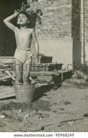 Vintage photo of young girl bathing in a bucket(fifties) - stock photo