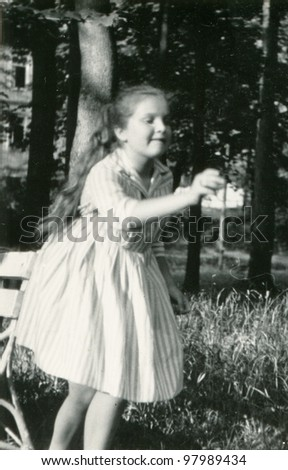 Vintage photo of young girl playing darts (sixties) - stock photo