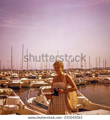 Vintage photo of young girl with a camera in Saint Tropez port, seventies
