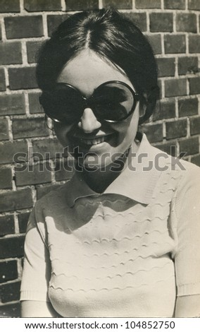 Vintage photo of young girl with big sunglasses (sixties) - stock photo