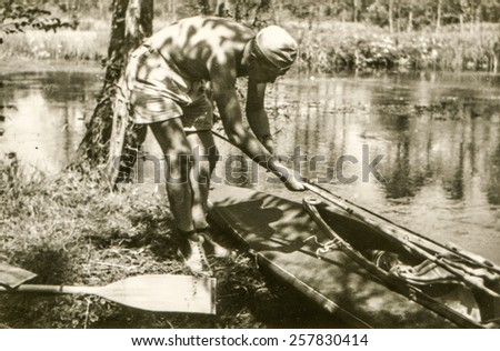 Vintage photo of young man during a canoe trip  (1960's) - stock photo