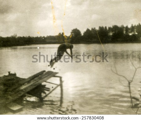 Vintage photo of young man plunging into the lake (1960's) - stock photo