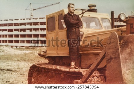 Vintage photo of young man standing on excavator (1960's) - stock photo