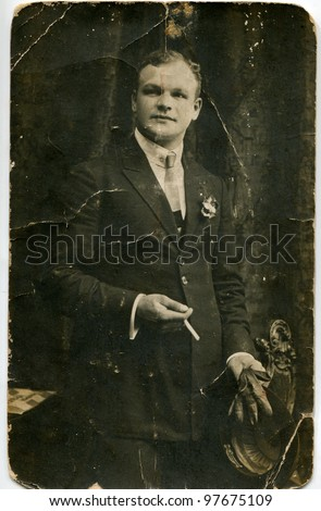 Vintage photo of young man with a cigarette, hat and gloves (circa 1920) - stock photo