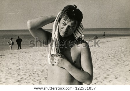 Vintage photo of young man with towel on beach (sixties)