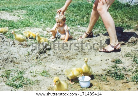 Vintage photo of young mother with a baby girl, 1981 - stock photo