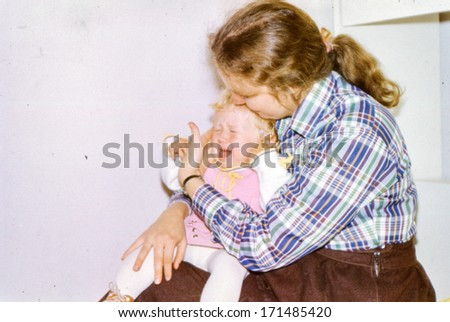 Vintage photo of young mother with a crying baby girl, 1981 - stock photo