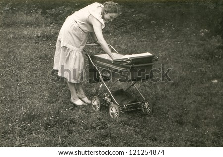 Vintage photo of young mother with pram (1981) - stock photo