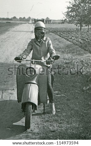 Vintage photo of young woman on scooter (fifties) - stock photo