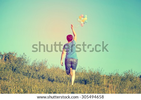 Vintage photo of young woman with colorful balloons in summer field - stock photo