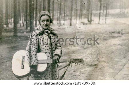 Vintage photo of young woman with guitar (sixties) - stock photo