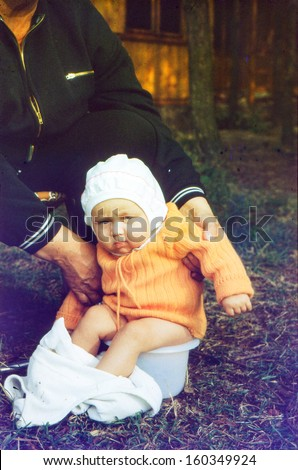 Vintage photo (scanned reversal film) - grandmother with baby granddaughter on potty, early eighties - stock photo