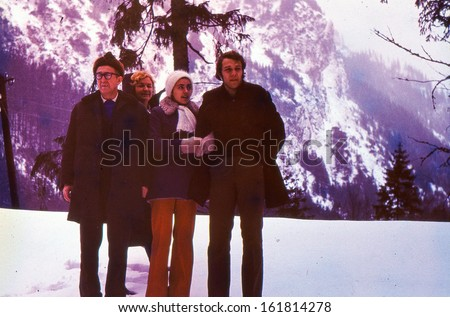 Vintage photo (scanned reversal film) - mature parents with son and daughter-in-law in mountains, seventies - stock photo