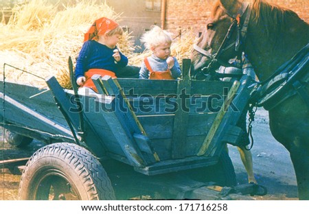 Vintage photo (scanned reversal film) of brother and sister playing in horse carriage (early eighties) - stock photo