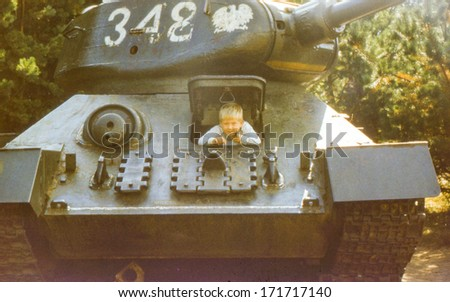 Vintage photo (scanned reversal film) of little boy in historical tank (early eighties) - stock photo